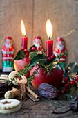 Weihnachtsäpfel mit Kerze, Lärchenzweig und Wacholderzweig, Plätzchen, Schokoladennikoläuse, Dattel und Erdnuss
