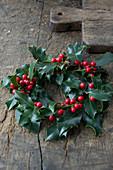 Kranz aus Ilex auf Holztisch als Weihnachtsdeko