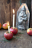 Candles in red apples in front of chocolate mould