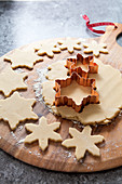 Cookie dough rolled out being cut out with a copper snowflake shaped cookie cutter