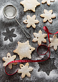 Two types of snowflake biscuits being dusted with icing sugar on a grey slate surface and an mini sifter and red Noel ribbon
