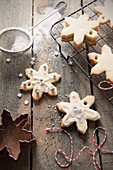 Homemade snowflake shaped Christmas tree decoration biscuits cooling on a wire rack and being iced and decorated in the backgroun is a mini sifter with icing sugar and a copper cookie cutter and bakers twine
