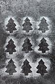 Abdrücke von Tannenbaumplätzchen in Puderzucker auf grauem Schieferuntergrund