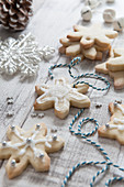 Iced homemade snowflake shaped christmas biscuits being treaded with blue and white bakers twine on a white wash wooden surface surrounded by Christmas tree decorations