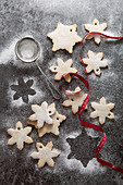 A number of snowflake shaped biscuits in the process of being dusted with icing sugar on a grey slate background mini sifter and red Noel ribbon