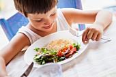 Kind isst Kichererbsenbratling mit Salat
