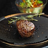 Beef fillet steak on a grill in front of a salad bowl