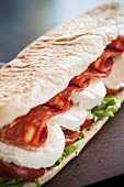 A sandwich with mozzarella, spicy salami, lettuce and tomatoes