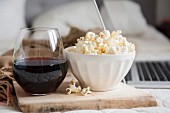 A bowl of popcorn and a glass of red wine near a laptop