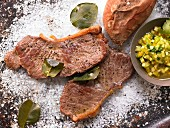 Steaks on a bed of coarse salt with sweet potatoes and vegetables