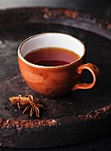 Hot tea with spices on dark background