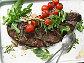 A rump steak with tomatoes and rocket