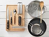 Verschiedene Küchenutensilien: Topf, Pfanne, Sieb, Messbecher, Reibe, Messer, Löffel