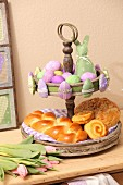 Pastries on vintage cake stand and green and lilac Easter ornaments