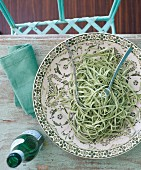 Green tagliatelle on a patterned plate (seen from above)