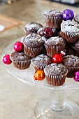 Muffins with Christmas baubles on a cake stand
