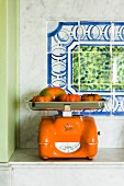 Tomatoes in orange kitchen scales in a tiled kitchen alcove