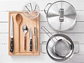 Various kitchen utensils: pots, sieves, measuring cups, knives, spoons