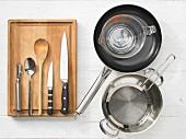 Verschiedene Küchenutensilien: Pfanne, Messbecher, Topf, Sieb, Sparschäler, Messer, Löffel