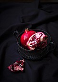 Two pomegranates in a metal bowl, one whole and one cut open