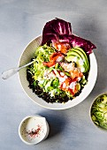 A bowl of wild rice topped with brussels sprouts, avocado, lobster meat and a honey and lemon buttermilk dressing