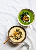A bowl of parsnip soup with hazelnut-parsley gremolata and parsnip chips next to a bowl of parsnip and broccoli soup with kale and croutons