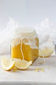 Lemon Curd in a glass jar with sliced lemons