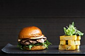 A juicy burger with bacon fois gras and lettuce in a bun served with a stack of chunky square cut chips on a black background