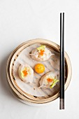 Steamed Chinese dumplings with prawns and fish roe in bamboo steaming basket with chopsticks