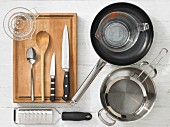 Various kitchen utensils: pot, pan, sieve, measuring cup, grater, citrus press