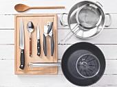 Verschiedene Küchenutensilien: Topf, Sieb, Pfanne, Messbecher, Dosenöffner