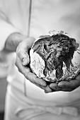 Bäcker hält kleinen Brotlaib in den Händen
