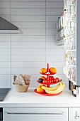 Fruit on red cake stand on white worksurface in kitchen