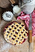 Lattice Top Cherry Pie with Powdered Sugar on Picnic Table