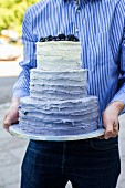 A man holding a three-tiered wedding cake