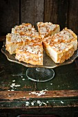 A cheesecake covered in caramel glazing and almond flakes