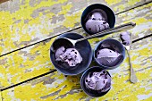 Several bowls of blueberry ice cream on a wooden background