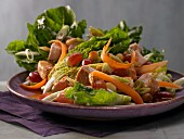 A colourful salad with chicken, grapes, carrot and macadamia nuts