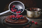 Chocolate cake with fresh berries and chocolate cream, served with vintage kitchenware