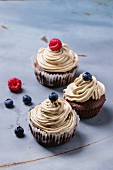 Chocolate cupcakes with butter coffee cream and fresh berries over gray metal surfave