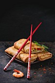 Fried spring rolls with vegetables and shrimps, served on squer ceramic plate with chopsticks