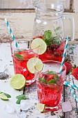 Selbstgemachte Erdbeerlimonade serviert mit Minze und Limetten in Gläsern und Krug