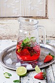 Glass jug of homemade strawberry lemonade, served with fresh strawberries, mint, lime and ice cubes