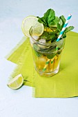 Glass of Iced green tea with lime, lemon, mint and ice cubes on green textile napkin