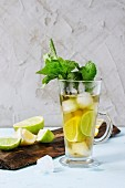 Glass of Iced green tea with lime, lemon, mint and ice cubes on wooden chopping board