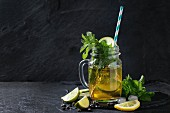 Glass mason jar of Ice green tea with lime, lemon, mint and ice cubes on black slate stone board