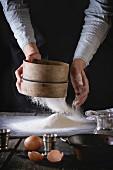 Person siebt Mehl mit Holzsieb auf Arbeitsfläche