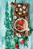 Ingredients for healthy breakfast. Quail eggs, bowl of muesli and strawberries on wood chopping board
