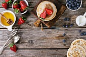 Pancakes with strawberries and blueberries, bowls of honey and jug of milk over old wooden background