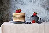 Breakfast with Pancakes with fresh strawberries and blueberries served on white linen tablecloth